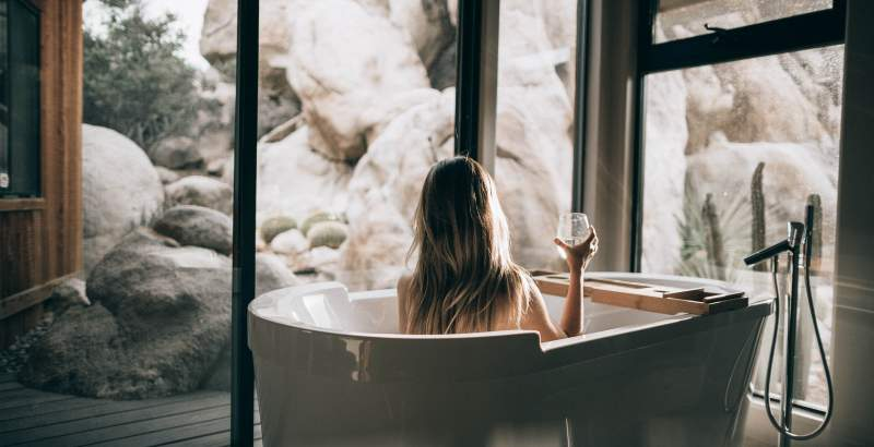 Woman in bath with a glas of mineral water watching the rock outside.